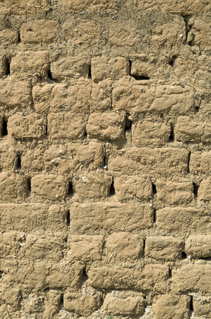 Old adobe wall closeup in sunny day photo