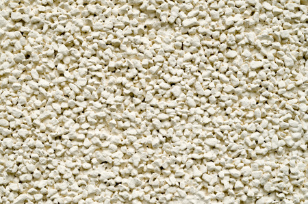 ecru: Ecru plaster from pebbles on wall closeup in sunny day Stock Photo