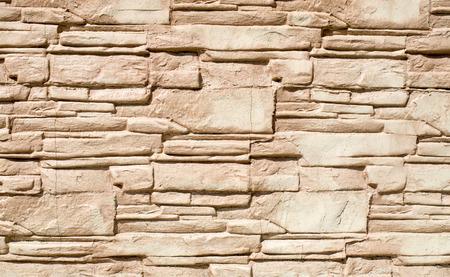 Decorative relief cladding slabs imitating stones on wall closeup