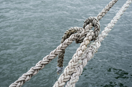 tightened: Old ship ropes tightened closeup in cloudy day