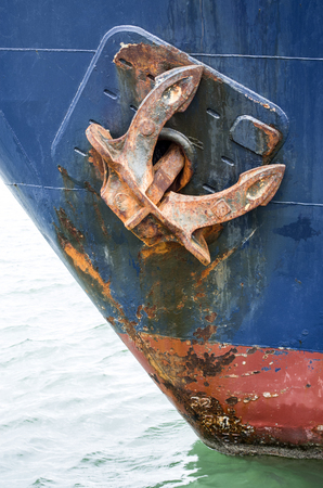 Rusty anchor of old blue ship closeup in port
