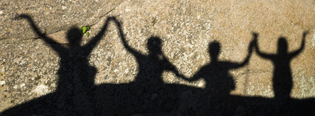 friend nobody: Shadows of happy people with arms raised on rock in sunny day