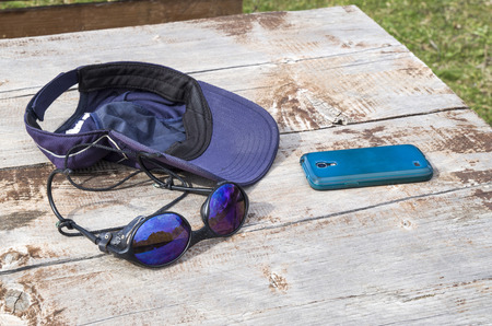 indispensable: Sunglass, baseball cap and mobile phone on table in hiking Stock Photo