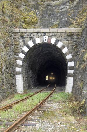 가 날에 철도 돌 터널에서 열차에 조명