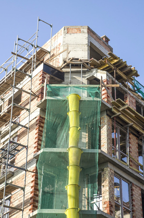 New construction with metal scaffolding and plastic debris chute