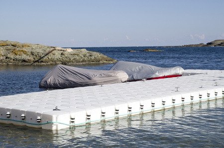 pontoon: White plastic pontoon for boats and two covered boats in sunny day