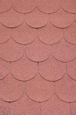 Roof with red bitumen shingles closeup in sunny day