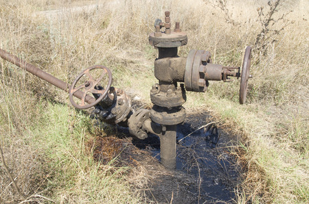 Old oil drilling on the meadow in sunny day