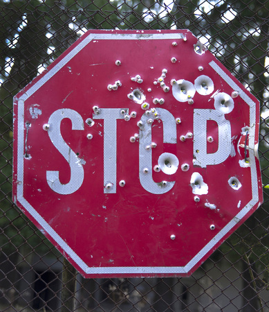 Stop sign with many bullet traces closeup