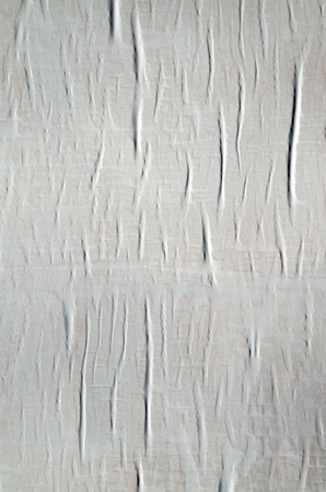 White paper glued to the wall closeup  in sunny day