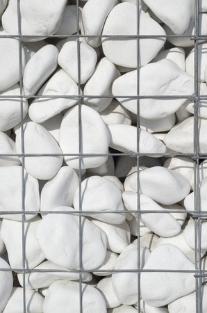White stone in new iron mesh closeup  in sunny day  Stock Photo