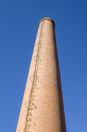 Chimney of bricks with a metal ladder in the sky