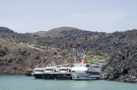 Many wooden ships on port of Nea Kameni volcanic island near Santorini