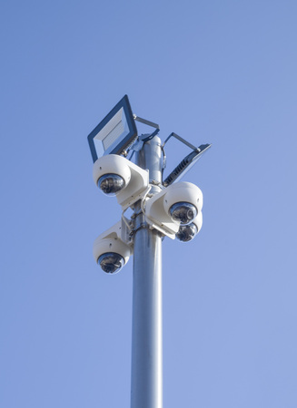 Four CCTV dome security cameras and two LED floodlight on a pole in sky Stock Photo