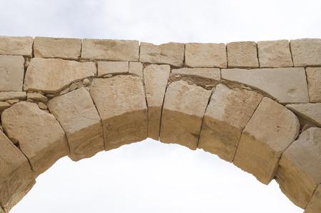 Arco de piedra antigua y piedra angular en el cielo de cerca