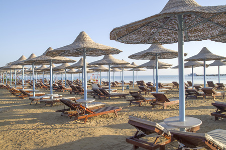 Many beach umbrella from wicker and lounge chairs, Hurgada, Egypt
