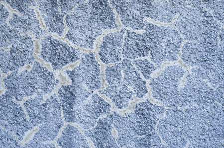 Old cracked blue coarse relief plaster on wall closeup