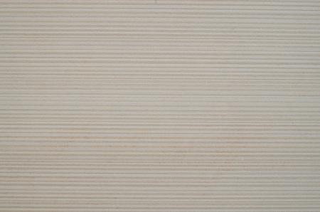 Ecru ceramic tile with horizontal lines on wall closeup