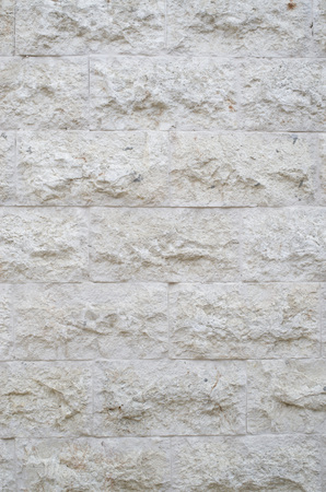 New rough stone wall closeup in sunny day