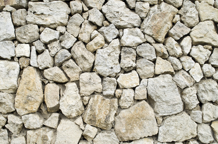 Old rural stone wall closeup in sunny day