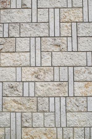 New white decorative stone wall closeup in sunny day