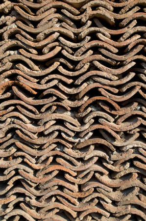 Wall of old brown roof tiles in sunny day