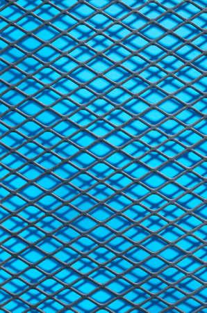 Metal grid of rhombuson blue background close up Banque d'images