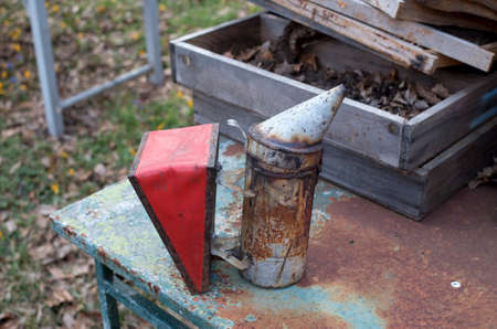 Old metal red bee smoker close up