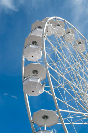 White Ferris wheel in the blue sky  with clouds