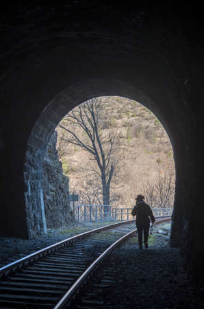 Man coming out of a dark stone railway tunnel Banque d'images