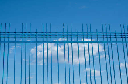 Blue decorative metal fence against the sky with clouds Banque d'images