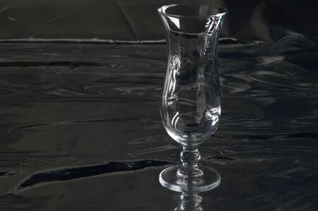 Still life with one single modern transparent and fragile glass on a table with a black background Stok Fotoğraf