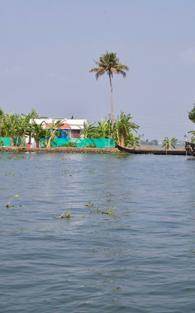 Kochi & Alleppey on a sunny summer day with a clear sky. Panorama of the backwaters in rural Kerala (india) with palm trees, untouched nature, small houses & a fishing boat on the waterway Stock Photo