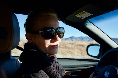 Pretty blonde caucasian woman driving a BMW car on a highway in Arizona (USA) wearing sunglasses and a black sweater