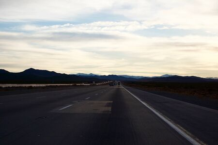 Scenic car road trip travels from California to Arizona (United States of America): Empty highway with minimal traffic on a sunny day with a clear blue sky with shite clouds