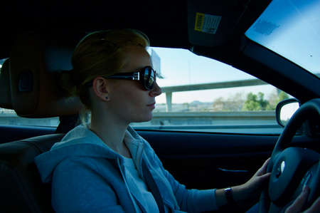 Pretty blonde caucasian woman driving a  car on a highway in Arizona (USA) wearing sunglasses and a black sweater Stok Fotoğraf