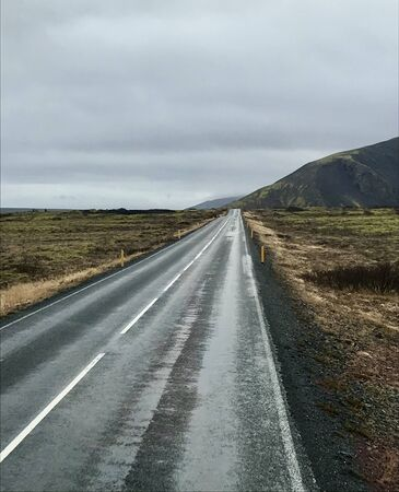 Tourism road trip journey along the Golden Circle from Reykjavik in Iceland (Europe): Scenic wilderness view & countryside with empty autumn road & clouds in the sky