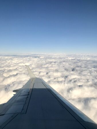 High up in the stratosphere, close to heaven: Above the white clouds on a scenic journey in an airplane flight of a vacation journey seeing the aircraft wing gliding over the bright cloudscape