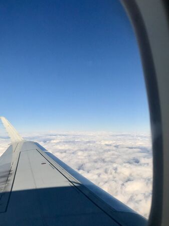 Beautiful view out of the airplane window inside the cabin of a business flight: The aircaft's wing is floating through an unreal heaven of spectacular fluffy white clouds in the atmosphere