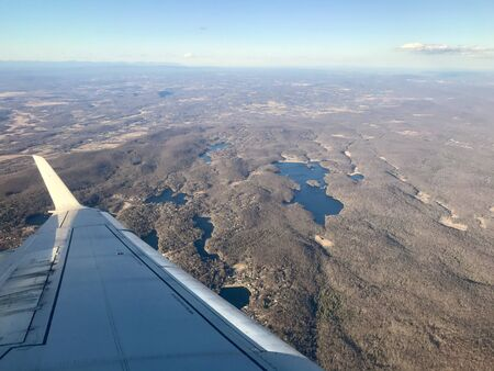 Beautiful aerial landscape panorama of upstate New York / Northern New Jersey from an airplane flying over rural lakes, green parks, valleys with forests & scenic mountains