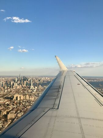 Vertical aerial view from an airplane wing of New Jersey landmarks & the urban downtown Manhattan metropolis' buildings & cityscape (New York City in the United States of America) in the background Stok Fotoğraf