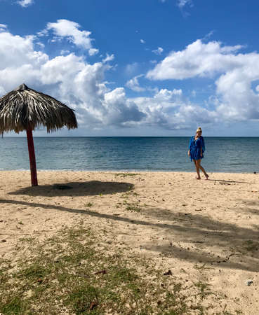 Pretty blonde female model on the sandy beach of Playa Ancon in Cuba in a panorama of a tropical paradise enjoying her relaxing vacation