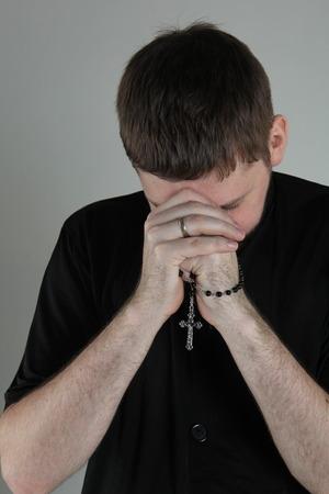różaniec: Katolicki ksiądz modli się z różańcem