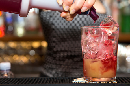a close up of a barman making a tequila sun rise in a tumbler glass. Barmaid is pouring some red syrup into the glass. 版權商用圖片