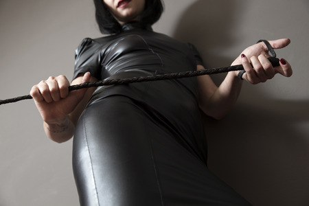 A black dressed woman with a riding crop in her hands