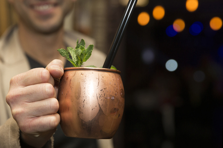 A men is holding a moscow mule, with focus on the drink. Imagens