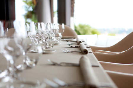 Closeup Of An Elegant Table Set In Fron Of A Big Window. Wine Glasses,