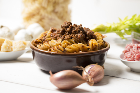 horizontal closeup of traditional italian pasta with bolognese sauce with all ingredients next to it, pasta is served in a terracotta brown plate on a white wooden table