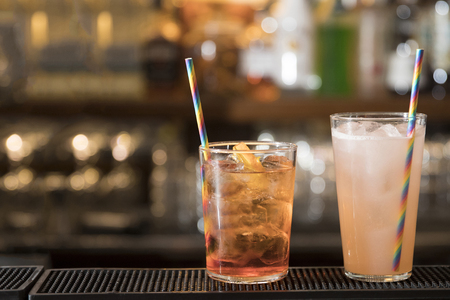 closeup of a bar counter, two colorful cocktails ( spritz and pink grapefruit cocktail) with nice drinking straw. subjects and focus on the right