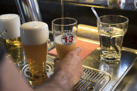 PIACENZA, ITALY - JUNE 15, 2018: closeup of a barman tapping a  Guinness Hop House 13 Lager behind a bar counter Editorial